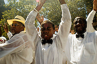 "Several hundred members of the United House of Prayer for All People, a non-denominational Pentecostal church, gather in Harlem in New York on Sunday, August 3, 2008 for a mass baptism. The church, which has held the baptisms on West 115 street since 1937, uses a fire hose to spray the congregation with city water blessed by the church's bishop. The ceremony is accompanied by music played by several brass ""shout"" bands. (© Frances M. Roberts)"