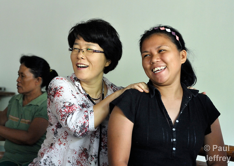 The Rev. Grace Choi is a United Methodist missionary serving in the Philippines, where she is community health worker in the outreach programs of Harris Memorial College. A nurse and a native of Korea, she also teaches piano and voice at the music department of the school. Here she examines a woman during a group discussion of women's health in the Upper Javier neighborhood of the town of Taytay, where Choi carries out health work. .