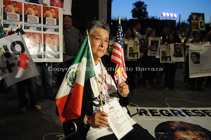 """Phoenix, Arizona - Maria Trujillo Herrera arrived to Phoenix from California as part of the """"Caravan for Peace with Justice and Dignity"""" to create awareness about her four missing sons. In this image she sits holding the Mexican and the U.S. flag as she listens to speakers during a rally and vigil held at the Civic Space Park. Two of her four sons - Raul and Jesus Salvador- went missing in August 2008 after going to a business trip to the Mexican state of Guerrero. Her other sons -Luis Armando and Gustavo- disappeared during a trip to the state of Veracruz in September 2010. The """"Caravan for Peace with Justice and Dignity"""" stopped in Phoenix on Wednesday, August 15, 2012 as it travels across the United States as a way to create awareness in the United States about the failed drug war in Mexico that has left more than 70,000 dead. The caravan is led by Mexican poet, essayist, novelist, and journalist Javier Sicilia, whose son Juan Francisco Sicilia Ortega son was brutally murdered along with six other students in Morelos, Mexico by members of a drug cartel on March 28, 2011. In response, Sicilia created the Movement for Peace with Justice and Dignity --popularly known as ¡Ya Estamos Hasta la Madre! or We Have Had It!-- calling for an end the drug cartels bloodshed. Photo by Eduardo Barraza © 2012"""