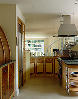 This horse-shoe shaped kitchen has marquetry veneer cupboards and roll-topped cabinets to store appliances