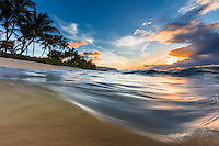 An above-and-below view of a wave meeting the shore as the sun sets over Waialua Beach, Mokuleia, O'ahu.
