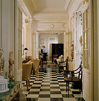 View from the hall through open double doors into the living room which has a black and white marble floor