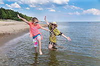 Mother and daughter in water with raised arms. Casual clothing.  Lake Peipsi in Estonia.