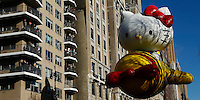 USA, New York, Nov 28, 2013. People try to watch the Hello Kitty balloon floats while it takes part in the 87th Macy's Thanksgiving Day Parade in New York City. Photo by VIEWpress/Eduardo Munoz Alvarez
