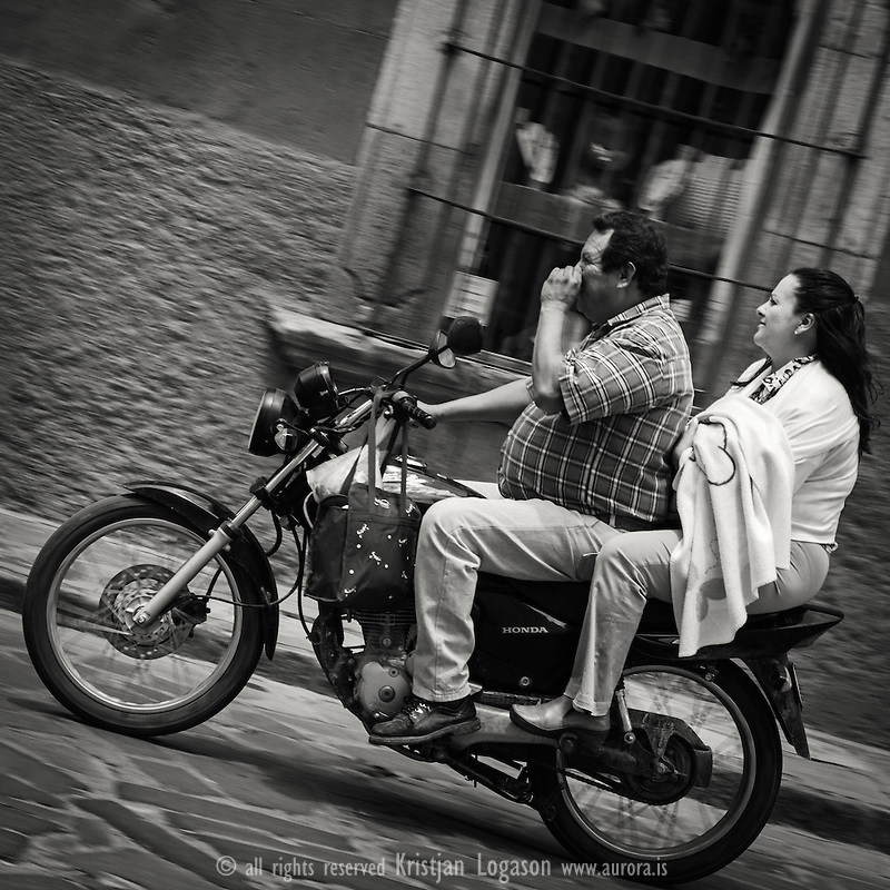 Family traveling on motorbike in San Miguel de Allende The man is in front picking his nose while the woman sitting behind him holds a child in here hands
