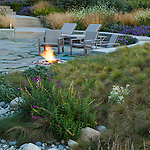 Outdoor image with curved stone patio, firepit, and surrounding meadow-like garden