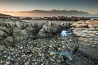 Limestone rock formations on Kaikoura coastline at sunset with Seaward Kaikouras mountains in background, Kaikoura, Marlborough Region, South Island, East Coast, New Zealand