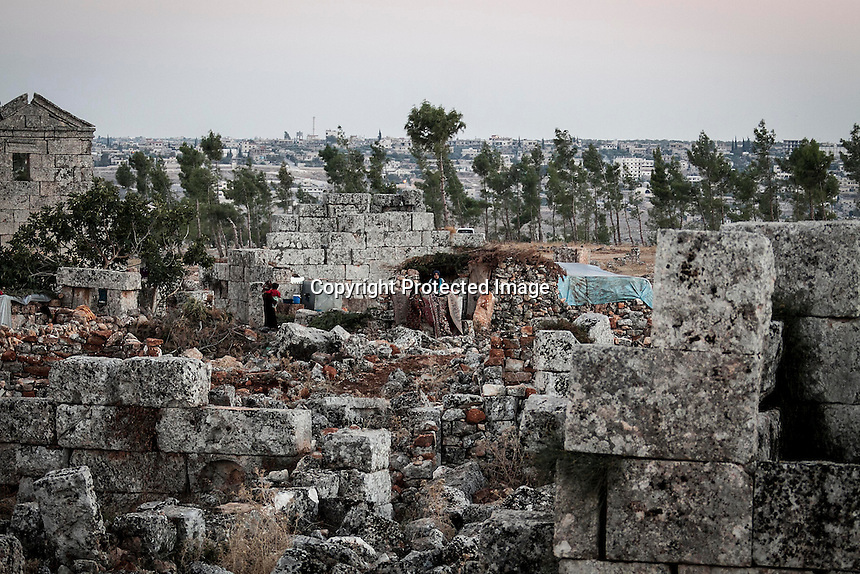 """In this Friday, Sep. 27, 2013 photo, shows a Syrian displaced family at the Kafr Ruma, an ancient roman ruins used as temporary shelter by those families who have fled from the heavy fighting and shelling in the Idlib province countryside of Syria. Dozens of families settled in the ancient ruins known as """"The Forgotten City"""" and declared human heritage by UNESCO, when the clashes between opposition fighters and government forces broke out in the region since more than two years ago. (AP Photo)"""