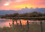 Idaho, Eastern, Driggs. Morning color lights up the sky above the Teton Range and reflects in the Teton River in autumn.