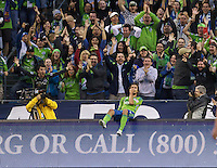 Seattle Sounders FC forward Roger Levesque celebrates his second goal by somersaulting backwards off a reader board during play against the New York Red Bulls at Qwest Field in Seattle Saturday June 23, 2011. The Sounders won the game 4-2.