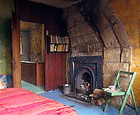 In the guest room a Victorian cast-iron fireplace has been built into the massive stones and glows with cheerful warmth