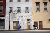Commuters wait for a bus outside the Pressley Memorial Church in downtown Yonkers in Westchester County in New York State on Saturday, March 23, 2013.  The daylighting of the Saw Mill River, combined with economic incentives is part of the plan by the city to revitalize the downtown area.  (© Richard B. Levine)