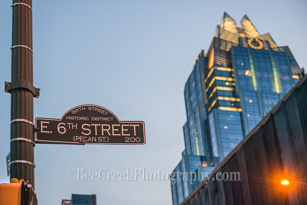 This is the east sixth street sign with the Frost Bank Building towering above in the historic 6st area in street in downtown Austin Texas.  This area was the commercial area of the town before the 1970's after that it was revitalize to become the new entertainment center for the city.    In the past the naming from east to west  streets was after trees so this was formerly call Pecan Street.  From this view you can see the 6th street sign and the Frost building which is a iconic building in the city on it on.  This street is one that help create the image of Austin as being the live music capital and over the years has gone through many transformations, but it still draws large crowds on the weekend and it can be almost crazy with students, tourist and other wildlife and  on Halloween and Mardi Gras and it is pretty much anything goes then so be prepared.