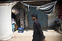 A man walks on the streets of the Orangi town slum. Pakistan is still a very conservative and male dominated society. With the political problems in the past few years caused by corruption and the consequences of the war on terror, conditions for women haven't improved at all. Karachi, Pakistan, 2011