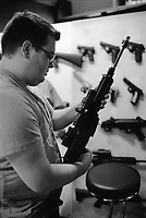 """Switzerland. Canton Obwald. Lungern. A young man is checking an automatic or semi-automatic assault rifle SG 550 in Brünig Indoor. The SG 550 is an assault rifle manufactured by Swiss Arms AG (formerly Schweizerische Industrie Gesellschaft) of Neuhausen, Switzerland. """"SG"""" is an abbreviation for Sturmgewehr, or """"assault rifle"""". The rifle is based on the earlier 5.56mm SG 540 and is also known as the Fass 90 or Stgw 90. An assault rifle is a selective-fire rifle that uses an intermediate cartridge and a detachable magazine. All weapons and handguns are for sale. 16.06.2016 © 2016 Didier Ruef"""