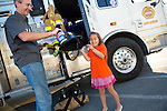 Lia Payne, 5, giggles as she receives a firefighter hat from her dad during National Night Out at Montclaire Elementary School in Los Altos, CA August 6.