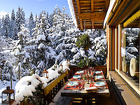 A table laid for al fresco dining has unrestricted views of the snow covered forest which surrounds the chalet