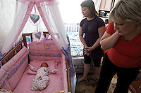 Photographs of Yulia Smirnova and her family at their home.  Yulia had her second child at the Moscow Planning Center and Reproduction Maternity Home. Yulia made the decision on a 2nd child based on the fact that she would get &quot;mother's capital&quot; and they could move out of the one room they share with their daughter in their mother-in-law's apartment.  Once she had the child she loved it so much she wondered why the money was the main motivation... because she was so happy to have the 2nd child..The maternity home delivers about 8000 children a year... about 20 a day or so... This is the most of any maternity hospital in Russia.  There are 117,000 delivered in 2009 in all of Moscow.  1,800,000 were born in Russia in 2009 which is 27,000 more than the deaths that year.  So Russia is basically at the replacement rate, but there are not as many breeders in the lineup moving forward... so the state has instituted a number of policies including free housing for immigrants and a one time payment of over $10,000 for a woman to have either the 2nd, 3rd or 4th baby.