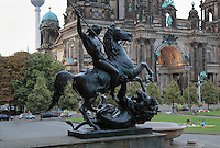 Statue of a man on horseback spearing a lion, Albert Wolff after a draft by Christian Daniel Rauch, 19th century, outside the Altes Museum or Old Museum, housing the Antique collection of the Berlin State Museums, Museum Island, Mitte, Berlin, Germany. In the background is the Berliner Dom or Berlin Cathedral, completed 1905 in Historicist style. The buildings on Museum Island were listed as a UNESCO World Heritage Site in 1999. Picture by Manuel Cohen
