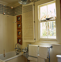 Towels hang from a heated rail in a nautical themed bathroom decorated with model boats