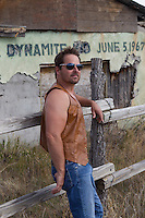 modern hippie leaning against a fence in New Mexico