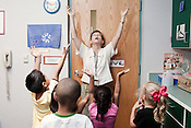Mary Hill leads her movement class in a post class stretching exercise at Project Enlightenment, a public pre-kindergarten program for at risk children. The program has been threatened with closure due to state wide budget cuts..