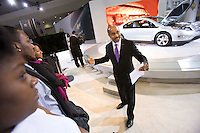 Slug:  GM/DC 2011 DC Auto Show.Date: 1- 27 - 2011 .Photographer: Mark Finkenstaedt.Location:  GM DC Auto Show - GM Vice President Global Design Ed Welburn with Howard University Student and media touring the auto show.  Presenting the award to Howard University's Dean james Mitchell