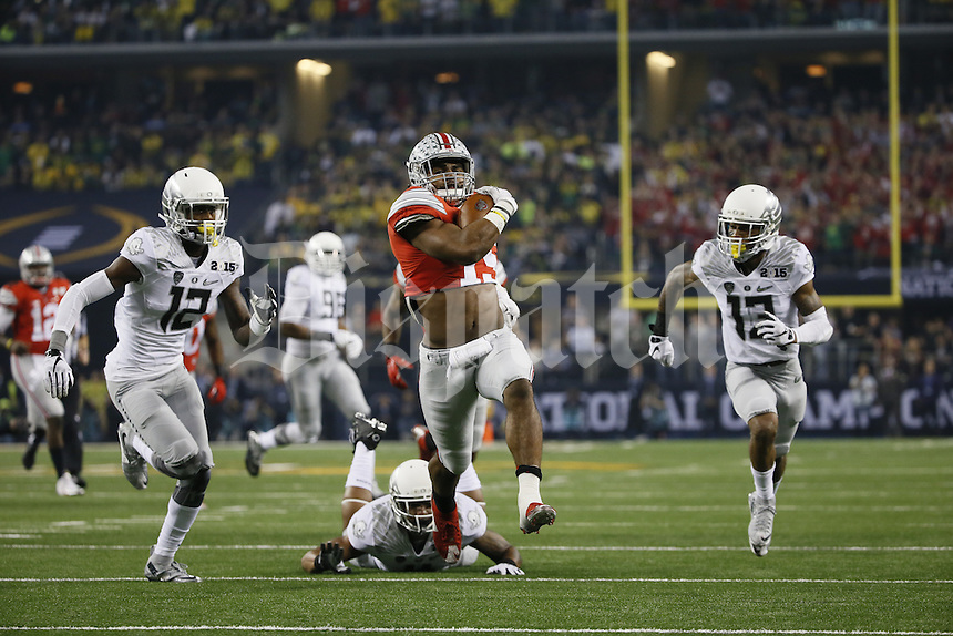 Ohio State Buckeyes running back Ezekiel Elliott (15) scores a 33-yard touchdown between Oregon Ducks defensive back Chris Seisay (12) and defensive back Troy Hill (13) during the first quarter of the College Football Playoff National Championship at AT&T Stadium in Arlington, Texas on Jan. 12, 2015. (Adam Cairns / The Columbus Dispatch)