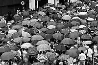 A crowd of believers walk down the street during a rainy day of Good Friday (Easter) in Manaus, Brazil, 9 April 2004. Amazonia is the world's largest dense tropical forest area. Since the 16th century the original indigenous people have been virtually pushed away or exterminated. The primal ancient unity between tribes and the jungle ambient has changed into a fight between the urban based civilization and the jungle enviroment. Although new generations of white and mestizo settlers have not become adapted to the wild tropical climate and rough conditions, they keep moving deeper into the virgin forest. The technological expansion causes that Amazonia is changing rapidly.