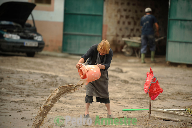 Beatriz, a resident of the southern city of Lorca, cleans a flooded street of Lorca, near Murcia, southeastern Spain, on September 30, 2012. Ten people in total have died in Spain in the regions of Andalusia and Murcia due to flash flooding brought on by downpours. The heavy rains have also damaged homes, caused the collapse of two bridges and forced roads to close. (c) Pedro ARMESTRE