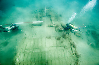 Two SCUBA divers setting up a grid to begin mapping a shipwreck. (Model Released)