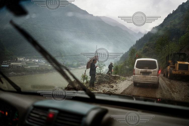 People watch as workers try to clear a blockage on the road that runs alongside the Nujiang River.