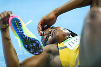 Jamaica Elaine Thompson takes her boots off after winning a sprint double while laying dazed on the field at the Rio2016 Olympic Stadium. <br /> Rio de Janeiro, Brazil on August 17, 2016.<br /> CAP/CAM<br /> &copy;Andre Camara/Capital Pictures /MediaPunch ***NORTH AMERICAS ONLY***