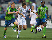 Seattle Sounders FC defender Tyson Wahl, left, and Vancouver Whitecaps FC  midfielder Shea Salinas race to the ball during play at Qwest Field in Seattle Saturday June 11, 2011. At right is Seattle Sounders FC defender Jhon Kennedy Hurtado . The game ended in a 2-2 draw.