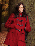 Portrait of a beautiful smiling woman in red coat leaning against a tree in autumn park