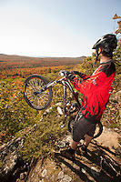 Mountain bikers take in the view of fall color in autumn at an overlook in Copper Harbor Michigan.