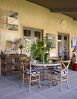 On the covered terrace an antique latticework sideboard has been juxtaposed with modern bamboo dining chairs surrounding the marble and wrought-iron table