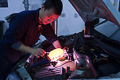 Students using an inspection lamp in the engine compartment, Motor Mechanics, Further Education College.