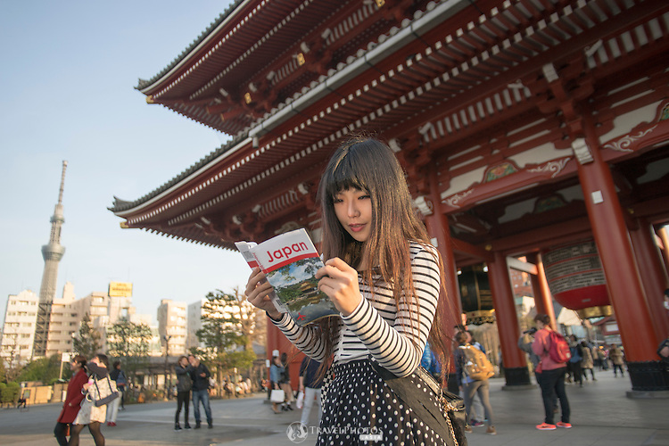 A young lady at Sensoji Temple with iconic lantern and Tokyo Skytree Tower in the background.