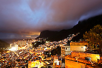 Night view from top of Favela da Rocinha, the largest favela in Brazil, located in Rio de Janeiro's South Zone between the high class districts of Sao Conrado and Gavea. Most of the favela is on a very steep hill, with many trees surrounding it. 69,161 (census 2010) people live in Rocinha, making it the most populous favela in Brazil. Although Rocinha is technically classified as a neighborhood, many still refer to it as a favela. It developed from a shanty town into an urbanized slum. Today, almost all the houses in Rocinha are made from concrete and brick. Some buildings are three and four stories tall and almost all houses have basic sanitation, plumbing, and electricity. Compared to simple shanty towns or slums, Rocinha has a better developed infrastructure and hundreds of businesses such as banks, medicine stores, bus lines, cable television, including locally based channel TV ROC (TV Rocinha), and, at one time, a McDonalds franchise. These factors help classify Rocinha as a favela bairro, or favela neighborhood.