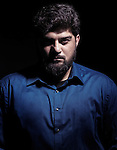 Dramatic portrait of a pakistani man looking at the camera isolated on black background