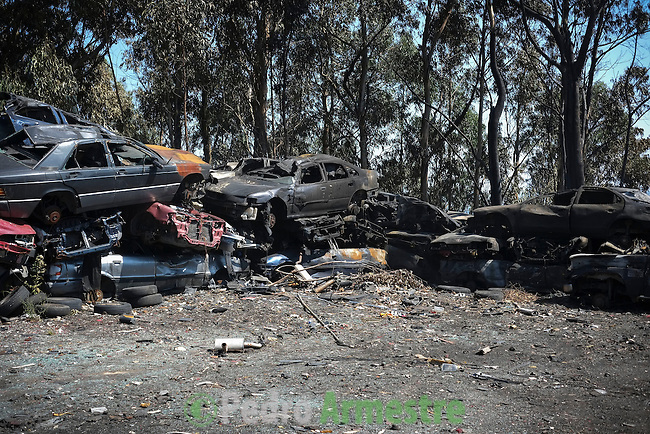Vehicles of a junkyard burned during a wildfire are seen in Riveira, near A Coruña on August 28, 2013. © Pedro ARMESTRE