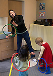 Berkeley CA Asian music teacher demonstrating rhythm movements using plastic rings to toddlers in extra-curricular music class