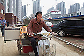 Chen Hua, 50, moves out of a village accommodation for her new urban home in the northeastern China.<br /> <br /> Her former village house was bulldozed by the government three years ago to make way for high-rise development. <br /> <br /> In the four years between her rural home being razed and the completion of her new city apartment, she and her family lived in temporary village housing such as this one. <br /> <br /> China is pushing ahead with a dramatic, history-making plan to move 100 million rural residents into towns and cities over the next six years &mdash; but without a clear idea of how to pay for the gargantuan undertaking or whether the farmers involved want to move.<br />