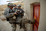 Private Dan Burris of the 82nd Airborne's 1/508 Parachute Infantry Regiment, Alpha Company, Third Platoon kicks in a door after staging a nighttime air assault into Sangin, Helmand province, the largest air assault in Afghanistan since the beginning of the war, on Thursday, April 5, 2007.