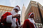 People dressed in merry christmas characters take part at the Santacon's Annual Festival passing the Empire State Building at Manhattan in New York, United States. 14/12/2012. Photo by ZAMEK