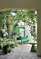 A restful garden room with trailing ivy and hydrangeas. A stone archway leads through to a sitting area with a paved stone floor.