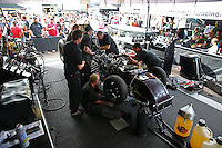 Feb 23, 2014; Chandler, AZ, USA; Crew members work on the car of NHRA funny car driver Alexis DeJoria in the pits during the Carquest Auto Parts Nationals at Wild Horse Motorsports Park. Mandatory Credit: Mark J. Rebilas-USA TODAY Sports