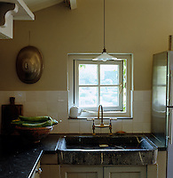 A sink made of granite is positioned beneath the small window in this rustic kitchen