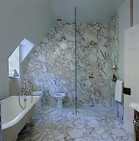 Marble lines the floors and walls of this elegant attic bathroom